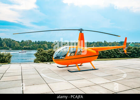 orange colored helicopter parked on a concrete slab under blue skies and water. - Stock Photo