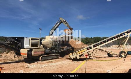 180726-N-ZH657-4042 ANDERSEN AIR FORCE BASE, Guam (July 26th, 2018) Seabees assigned to Naval Mobile Construction Battalion (NMCB) 11, Detachment Guam, use an excavator to load soil into a crusher. NMCB-11 is forward deployed to execute construction, humanitarian and foreign assistance, and theater security cooperation in the 7th Fleet area of operations. (U.S. Navy photo by Construction Mechanic 2nd Class Brittney Ebbert) - Stock Photo