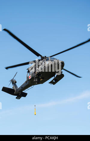 An Alaska Air National Guard UH-60 Black Hawk hovers above the landing zone during casualty evacuation training at Joint Base Elmendorf-Richardson, Alaska, July 19, 2018. Training was conducted by U.S. Marines with Delta Company, 4th Law Enforcement Battalion from Marine Corps Reserve Center, Billings, Montana. (U.S. Air Force photo by Airman 1st Class Caitlin Russell) - Stock Photo