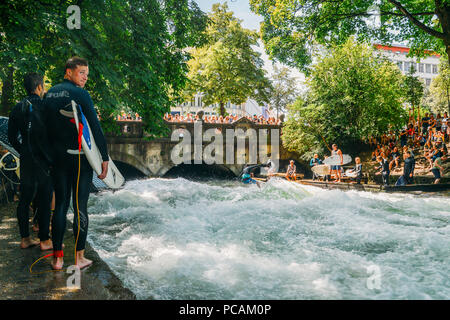 Surfer on the Eisbach in the English Garden with many spectactors - Stock Photo