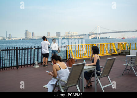Japanese people and foreign tourists enjoying a panoramic view of rainbow brdge at a wharf - Stock Photo