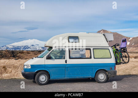 16 April 2018: Budir, Snaefellsnes Peninsula, West Iceland - Volkswagen T4 Campervan with bikes on the back, and the Snæfellsjokull Volcano in the bac - Stock Photo