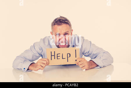 Young attractive frustrated and tired caucasian businessman holding help sign message exhausted, sad under pressure and stress isolated on white in un - Stock Photo