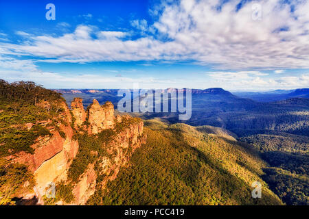 Three sisters rock cliffs natural landmark with Mt Solitude in a distance over massive valley seen from Echo point lookout at Katoomba town - Blue Mou - Stock Photo