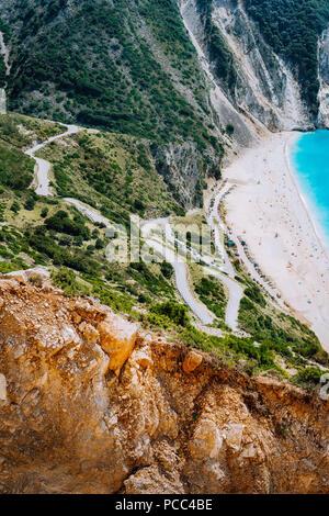 Serpentine zigzag road down to famous Myrtos Beach. Orange rocks ravine on side. Sunny beach from view point platform, Kefalonia, Greece. - Stock Photo