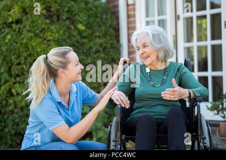 Carer Pushing Senior Woman In Wheelchair Outside Home - Stock Photo
