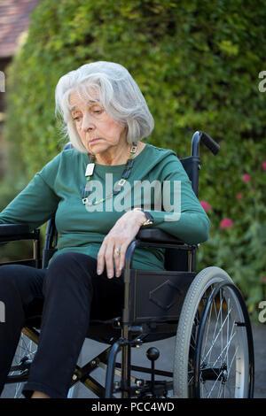 Depressed Senior Woman In Wheelchair Sitting Outdoors - Stock Photo