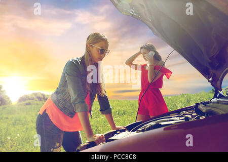 women with open hood of broken car at countryside - Stock Photo