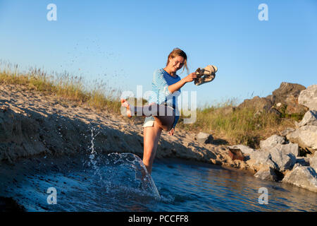 A cheerful dark-haired woman smiles, walks along the beach, kicks waves, sprays around a lot and enjoys the bright sun on a summer day. Concept of sum - Stock Photo