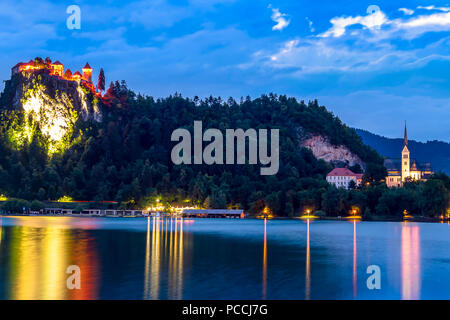 The Bled Castle lighted during blue hour overlooking the lake on a summer day. Slovenian castle on a cliff illuminated at night with water reflections - Stock Photo