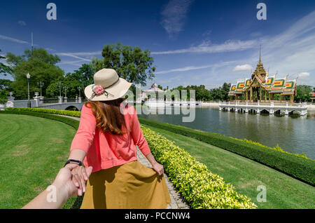 Portrait of Beautiful Asian girl leading her partner by hand to the famous Bang Pa-In Royal Palace. The place also known as the Summer Palace. - Stock Photo
