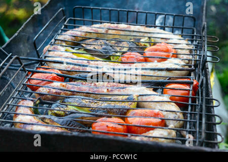 Pork sausages with vegetables are grilled on fire. Cooking dinner outdoors. - Stock Photo