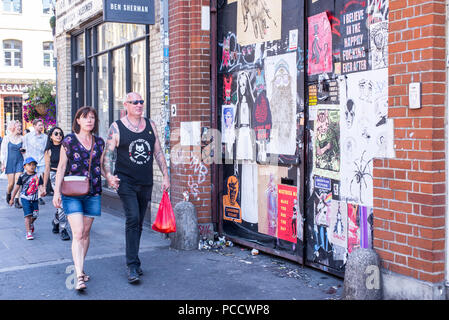 Male punk rock senior man holding hands with partner walking in front of wall covered in street art murals and posters in Commercial Street, in front  - Stock Photo