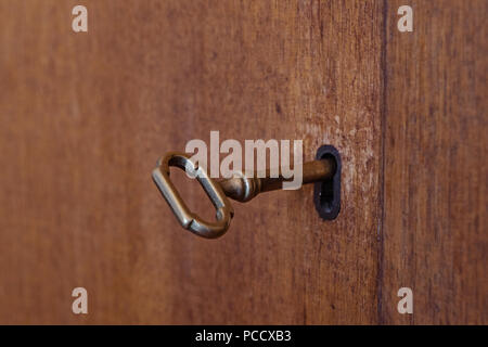 Old wooden cabinet with vintage key in keyhole, shallow depth of field selective focus, copy space - Stock Photo