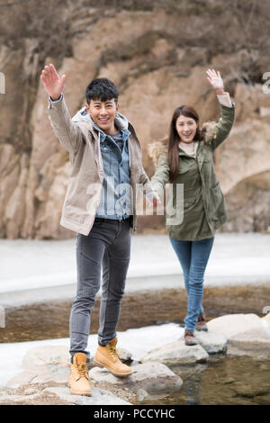 Happy young Chinese couple waving outdoors in winter - Stock Photo