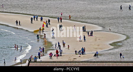 Different people doing different things - a Lowry-like scene on the sands of Scarborough's South Bay beach. - Stock Photo