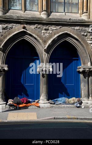London. Hackney. Shoreditch. Two homeless men sleep in a doorway. - Stock Photo