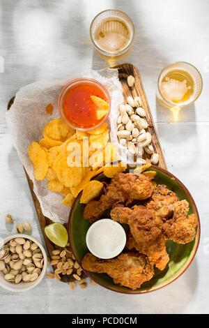 Fried chicken, beer and snacks to beer on a white wooden surface, top view - Stock Photo