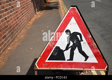Old, weathered, red and white triangular road safety sign Men At Work on the side of the road. Black person on white background symbol digging - Stock Photo