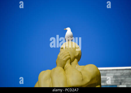seagull resting on a mute man monument in Gothenburg, Sweden. - Stock Photo
