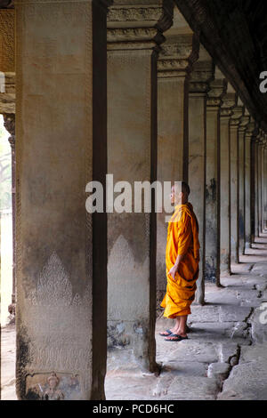 Buddhist monk in a colonnaded corridor in a temple in Angkor Wat, UNESCO World Heritage Site, Siem Reap, Cambodia, Indochina, Southeast Asia, Asia - Stock Photo