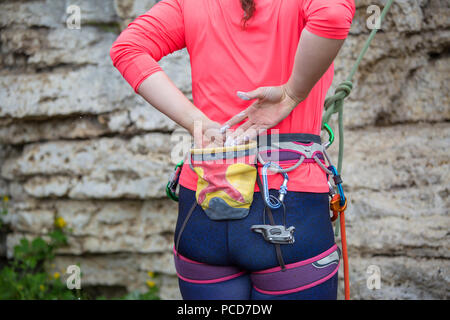 Photo from back of female climber standing next to mountain - Stock Photo