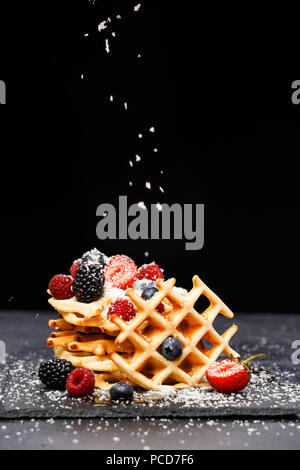 Photo of fresh viennese waffles with berries sprinkled with powdered sugar on blackboard on blank background - Stock Photo