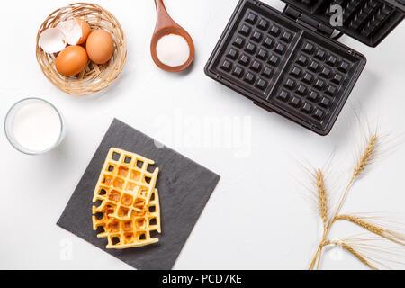 Photo on top of flour, eggs, waffle iron, spikes, fresh roasted waffles - Stock Photo