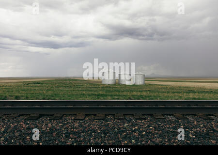Grain silos and storm clouds over vast farmland and prairie, train tracks in foreground - Stock Photo