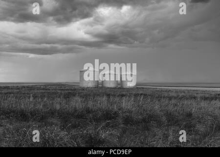 Grain silos and storm clouds over vast areas of farmland and prairie. - Stock Photo