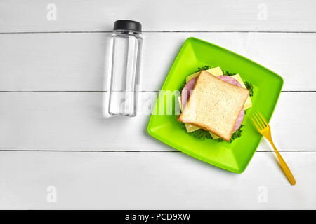 Cheese and ham sandwich, bottle of water on white wooden table. Healthy lunch idea concept. Top view. Still life. Copy space. flat lay - Stock Photo