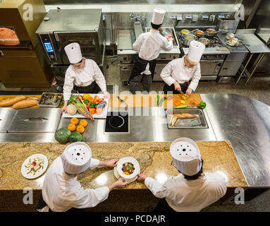 A view looking down on a crew of chefs working in a commercial kitchen, - Stock Photo