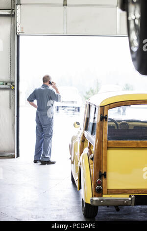 View from behind of an owner of a car repair shop on his cell phone. - Stock Photo