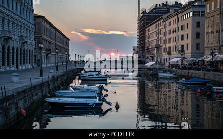 Trieste, Italy, 31 July 2018.  The sun sets over the Adriatic Sea as seen from the Canal Grande in downtown Trieste.  The navigable channel, perpendic - Stock Photo