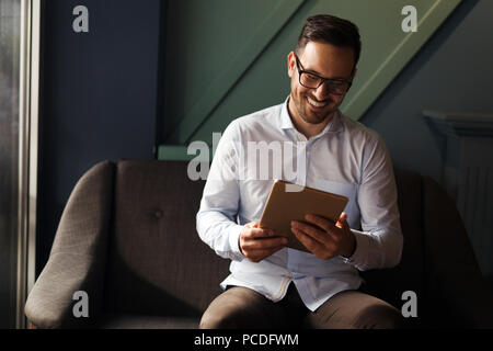 Businessman wearing glasses holding tablet - Stock Photo