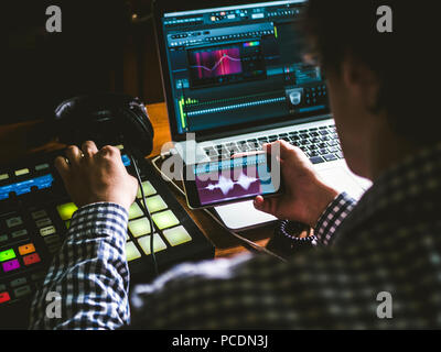 close up sound producer's hand holding phone and using app to create music in sound recording studio - Stock Photo