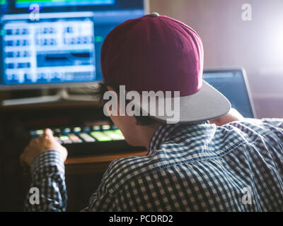 young smiling happy man in the sound recording studio working on the new track - Stock Photo