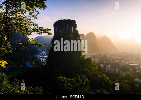 Beautiful sunrise over Yangshuo karst rocks and city near Guilin in China - Stock Photo