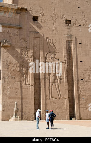 Tourists and a guide at the entrance to the Temple of Edfu, dedicated to Horus and Hathor, at Edfu, Egypt. Stock Photo