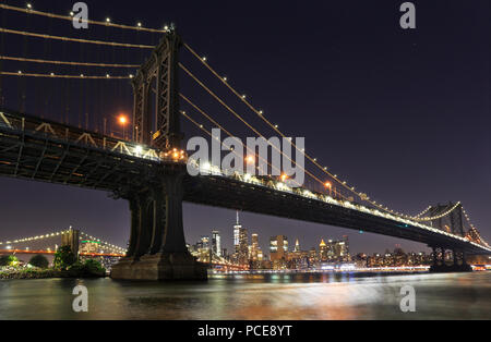 Panorama of  Manhattan and Brooklyn bridges and New York City with lights and reflections at night, USA - Stock Photo