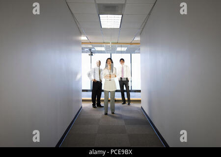 A portrait of a mixed group of business people standing at the end of a long hallway. - Stock Photo