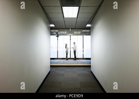 Male and female business people talkng and standing in front of a window at the end of a long hallway. - Stock Photo
