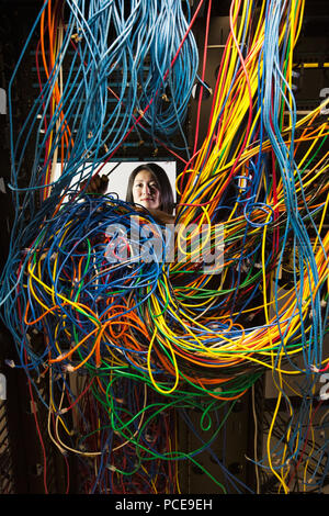 Asian female technician woking on a tangled mess of CAT 5 cables in a server room. - Stock Photo
