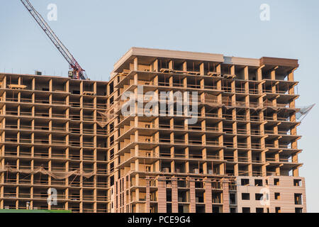 Tall Building Under Construction Under Cloudy Sunset. - Stock Photo