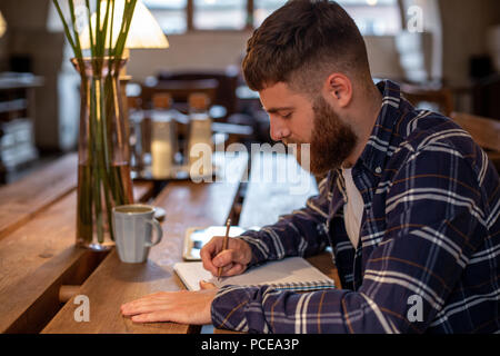 Young bearded businessman sits in cafe, home at table and writes in notebook, near lies tablet computer. Man is working, studying. - Stock Photo