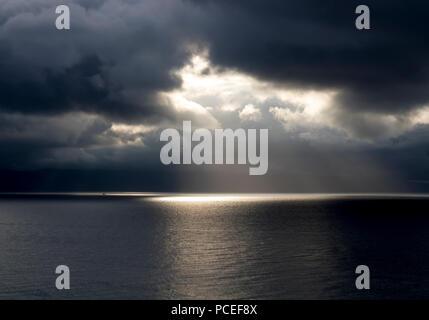 Sun Breaks Through Black Storm Clouds over Ocean - Stock Photo