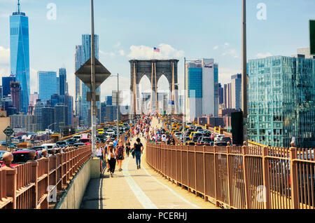 June 10, 2017.  New York City, New York.  Toursts and Traffic on the brooklyn bridge and the new york city skyline on a sunny day in the summertime. - Stock Photo