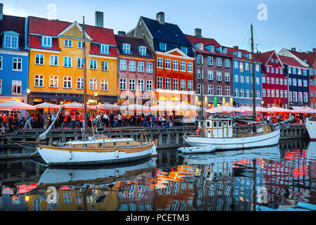 Sailboats moored by Nyhavn promenade illuminated at the evening, Copenhagen old town cityscape, Denmark - Stock Photo