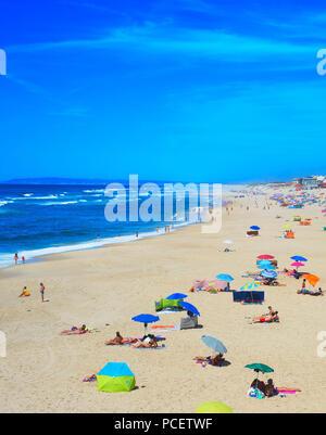 ESPINHO, PORTUGAL - JUL 30, 2017: People at the ocean beach in a high peak season. Portugal famous tourist destination for it's ocean beaches. - Stock Photo