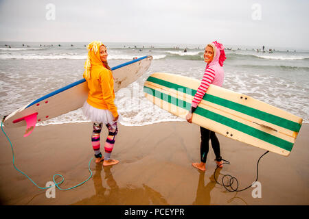 Wearing fanciful costumes  and hefting their surfboards, two young women and head for the ocean at a Halloween costumed surfing event in Huntington Beach, CA.  (Photo by Spencer Grant) - Stock Photo